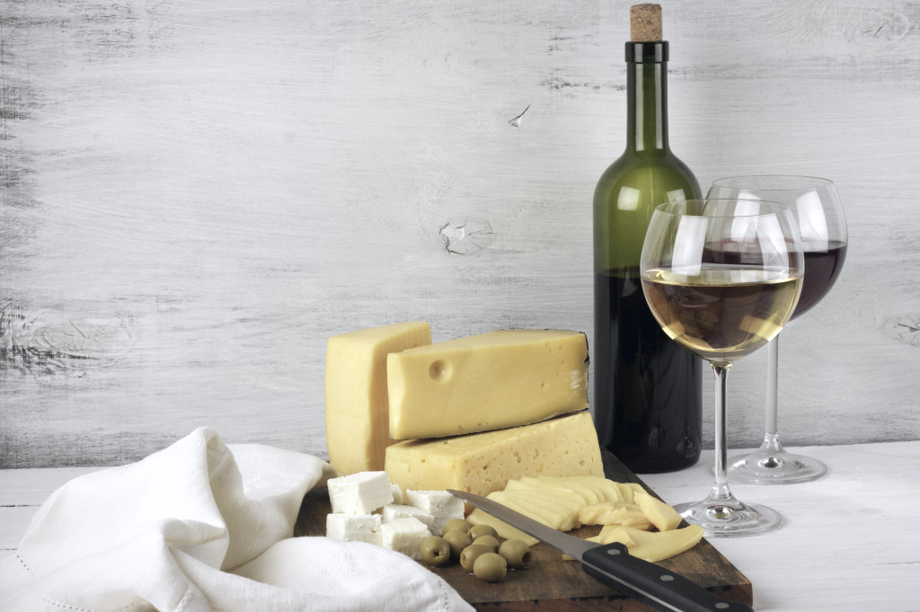 Assorted cheese with olives on board and red and white wine in glasses with bottle on rustic wooden background.